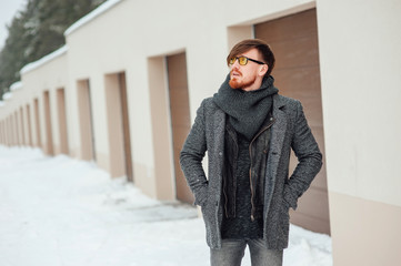 Stylish man in a coat on background of the house