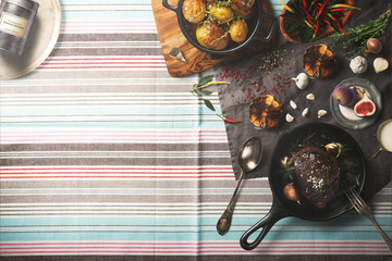 Overhead view of colorful roast vegetables, savory sauces and salt served with grilled t-bone steak on a rustic wooden counter in a country steakhouse created digital illustration