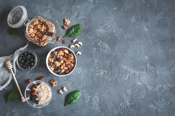 Healthy breakfast with muesli, blueberry, nuts on dark background. Flat lay, top view