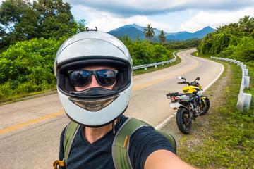 Island selfie wearing helmet and motorcycle in distance
