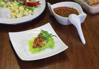 Nam Neung , Vietnamese food in white dish and sweet sauce with ingredients all put on dark wooden table