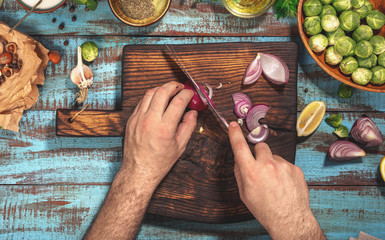 Man preparing healthy food on kitchen wooden table