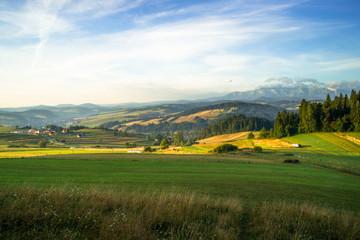 Pieniny i Tatry. Krajobraz wyżynny okolic Czorsztyna i Niedzicy. Tereny rolnicze w oddali Pieniny (po lewo) i Tatry Bielskie (po prawo)