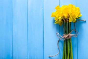 Spring easter background with daffodils bouquet on wooden table