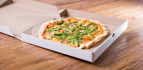 Italian pizza with green pepper in paper box tasty macro picture useful for background
