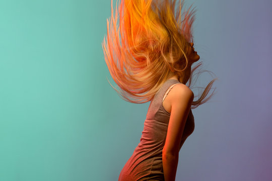 Profile of pretty blonde young woman shaking her hair