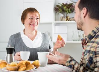 Elderly mother and son breakfast