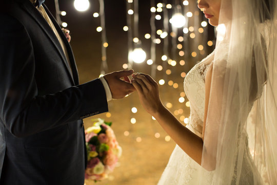 Evening wedding ceremony. The bride and groom holding hands on a background of lights and lanterns.