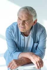portrait of pensive senior man in stylish shirt on white