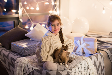 Very beautiful and charming little dark-haired girl in white sweater holds a live rabbit in the interior of the house. New year. Christmas. Hare. Studio.