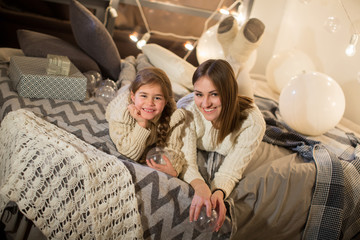 Beautiful mother and daughter lying on the bed on Christmas eve in the cozy interior of the house. New year.