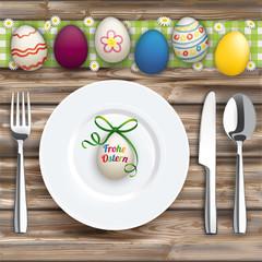 Frohe Ostern Teller mit Besteck und Ostereiern auf einem Holztisch
