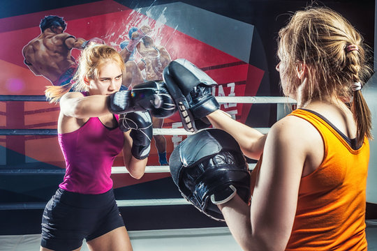 Young adult woman doing boxing training with her coach