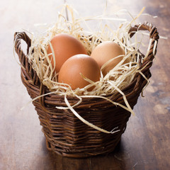 Three eggs in wicker basket on wooden background