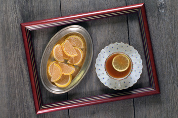 tea with lemon and marmalade in a frame on a wooden table