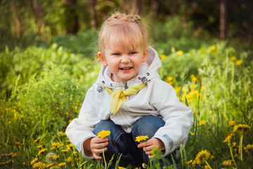 little girl on the dandelions meadow in spring day
