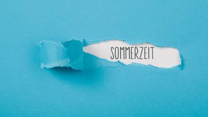 Sommerzeit Wort auf Papier hinter aufgerissenem blauen Karton