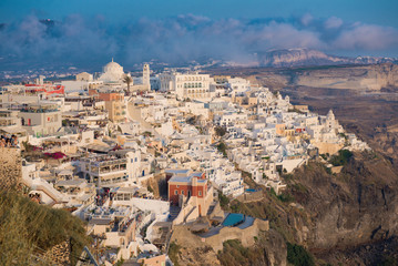 City on a rock, Santorini Island in the rays of the sunset, Sunset sun in tourist city on the island of Santorini. Architecture of island of Santorini,  Travel to Greece. season of romantic travel