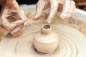 Women hands. Potter at work. Creating dishes. Potter's wheel. Dirty hands in the clay and the potter's wheel with the product. Creation. Working potter