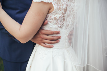 Wedding. The groom in a suit and the bride in a white dress standing side by side and cuddle each other in green garden