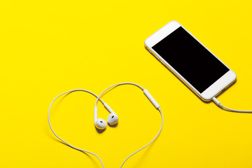 Close-up of smart phone with headphones on a yellow background. (Top view). Listen to music