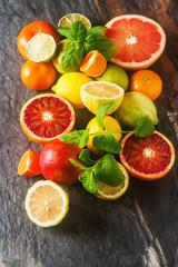 Citrus juice fruit and slices of orange, grapefruit, lemon, lime. Vitamin C. Black background