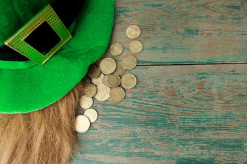 Happy St Patricks Day leprechaun hat with gold coins on green wood background. Top view