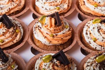 Vanilla cupcakes with orange and white creamcheese and chocolate decor. Selective focus. Shallow depth of field