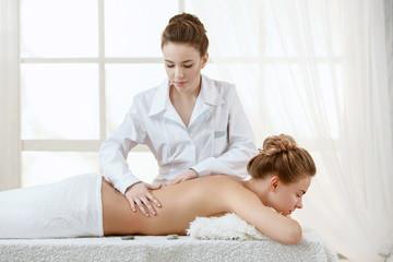 Beautiful Blond Woman Getting Spa Treatment. Masseur Brunette Girl Doing Massage
