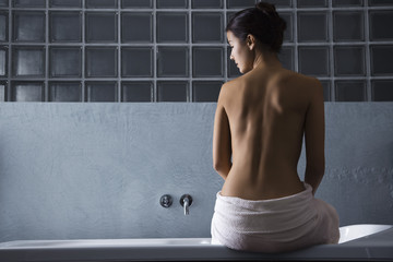 Woman sitting on edge of bathtub, rear view