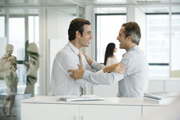 Businessmen holding each other's arms with excitement