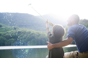 Father and son fishing, boy caught fish in fishing net