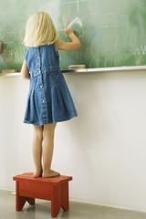 Little girl standing on stool, scribbling on blackboard, rear view
