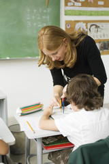 Teacher showing elementary student how to draw using compass