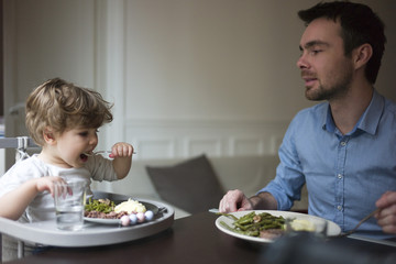 Father and toddler son eating dinner together