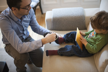 Father putting shoes on young son