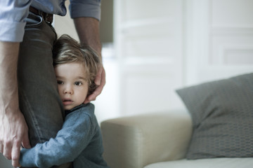 Cute boy holding father's leg at home
