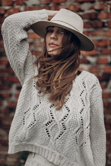 stylish hipster  woman posing in knitted sweater on background of brick wall, holding hat. atmospheric sensual moment. boho country fashionable look. free people