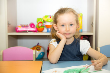 Adorable child girl draws a brush and paints in nursery room. Kid in kindergarten in Montessori preschool class.