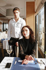 Vertical image of Woman in restaurant with man behind her