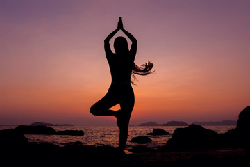 Woman practice Yoga during Sunrise at sea