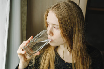 young beautiful redhead woman drinking pure still water from the glass