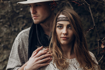Beautiful brunette gypsy girl, hipster woman in boho white sweater holding hands with handsome man in cowboy hat, free couple outdoors