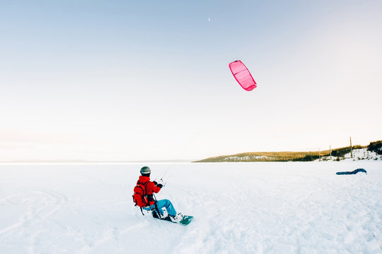 Snowboarder with a kite rides on a frozen lake on free ride. Kola Peninsula, Russia