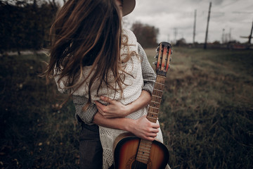 Hipster musician couple hugging in field, handsome man embracing gypsy woman in white dress, guitar closeup