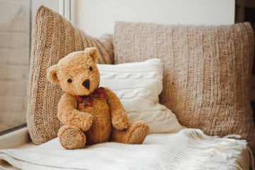 A beautiful soft toy bear sits on the bed