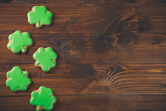 Beautiful background for St. Patrick's day with clover gingerbread on a wooden table. Free space