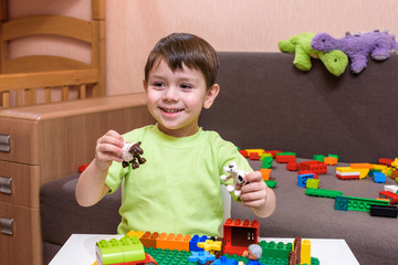 Little caucasian child playing with lots of colorful plastic blocks indoor. Kid boy wearing shirt and having fun building creating