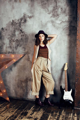 young pretty woman waiting alone in modern loft studio, fashion musician concept, lifestyle people