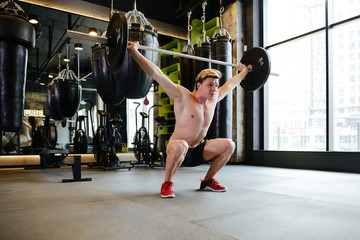 Athletic man doing exercise with barbell